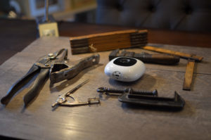 A Nanit baby monitor camera on a workbench with tools