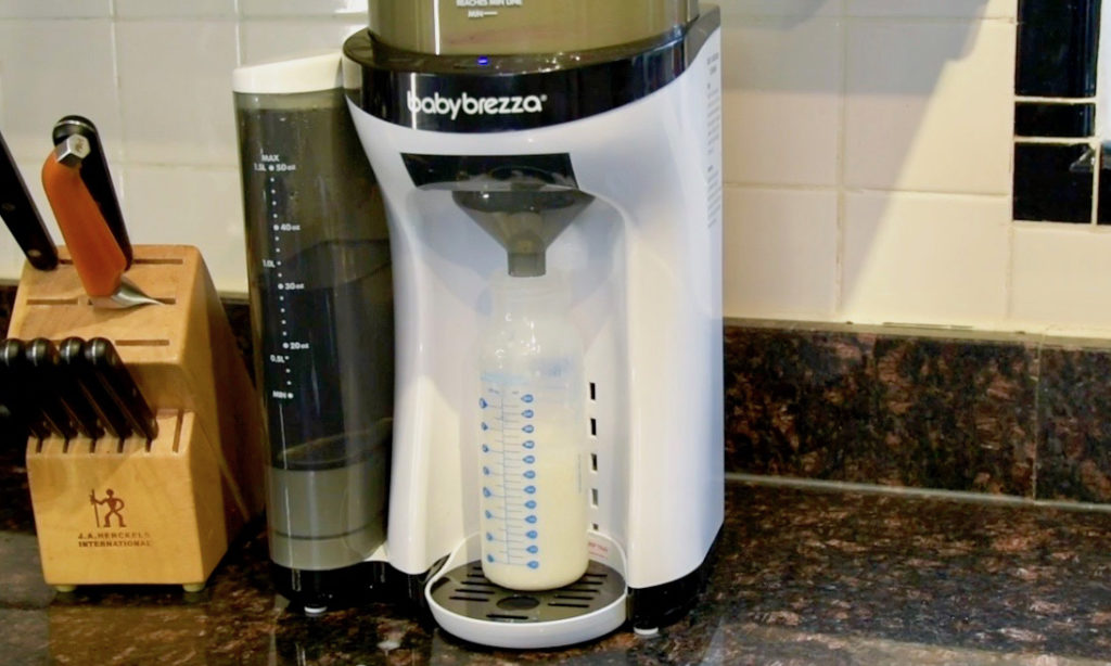 The Baby Brezza Formula Pro on a counter in kitchen next to some knives