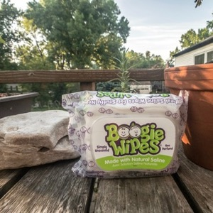 A container of Boogie Wipes on a wooden table outside