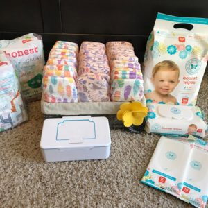 Diapers and wipes from The Honest Company arranged on a carpet