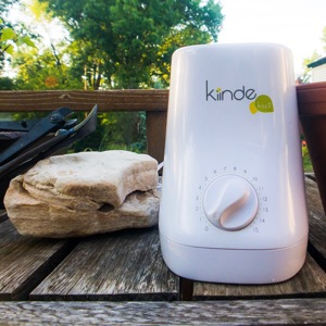 A Kiinde bottle warmer on a wooden table outside