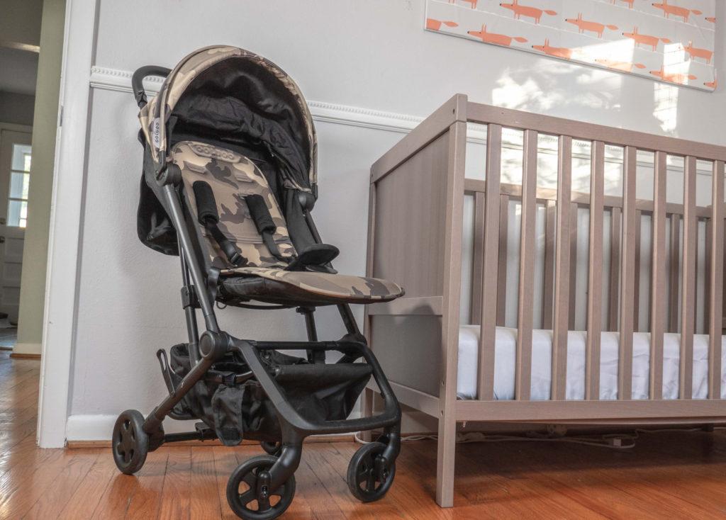 Colugo Compact Stroller next to a crib