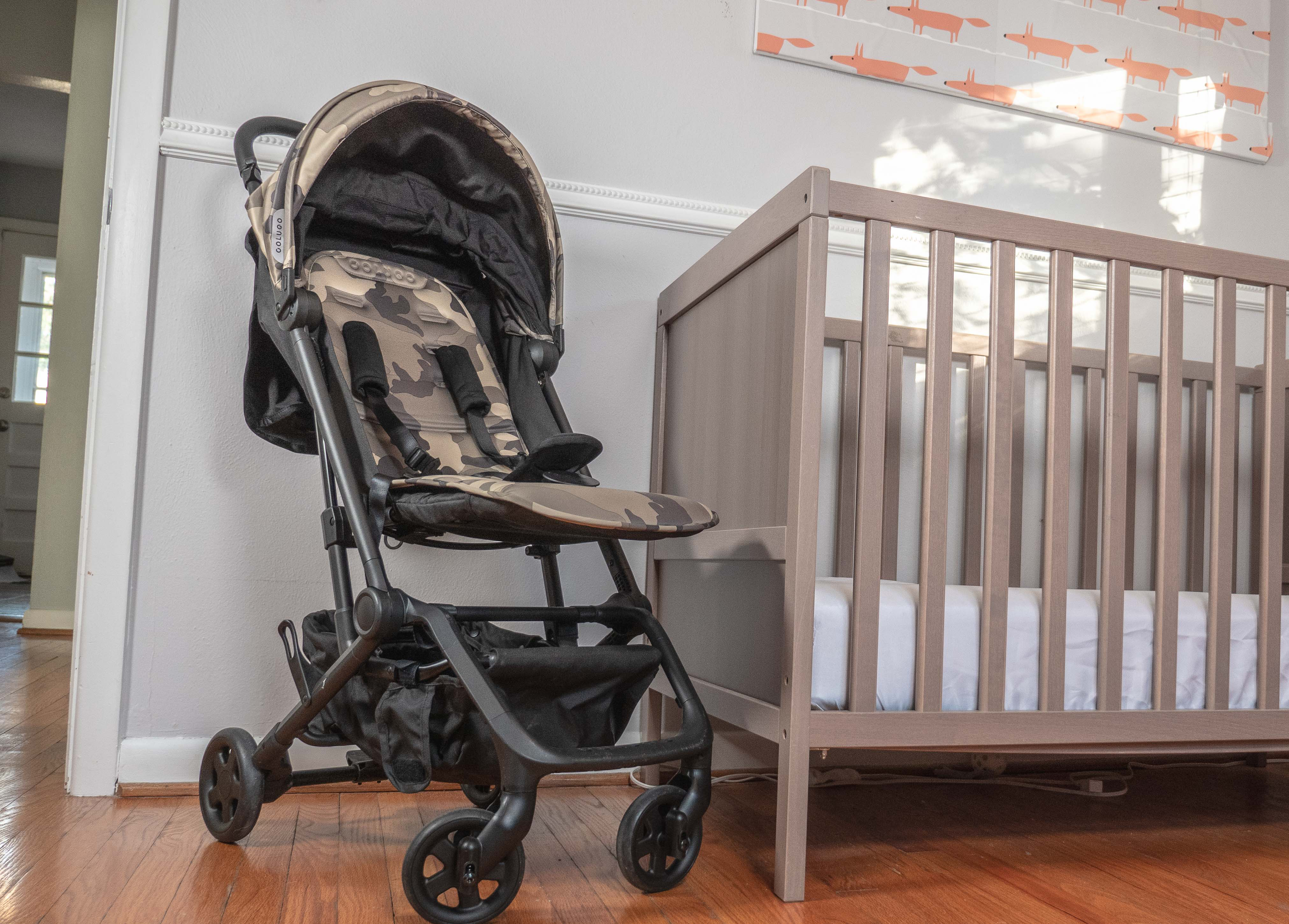 Colugo Compact Stroller next to a crib