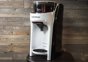 Baby Brezza Formula Pro Advanced on a table in front of a wood-paneled wall