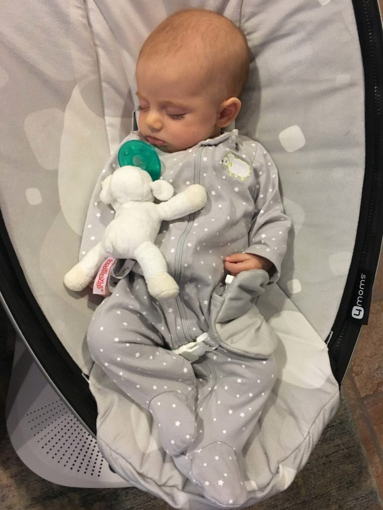 A baby in a Mamaroo with a pacifier