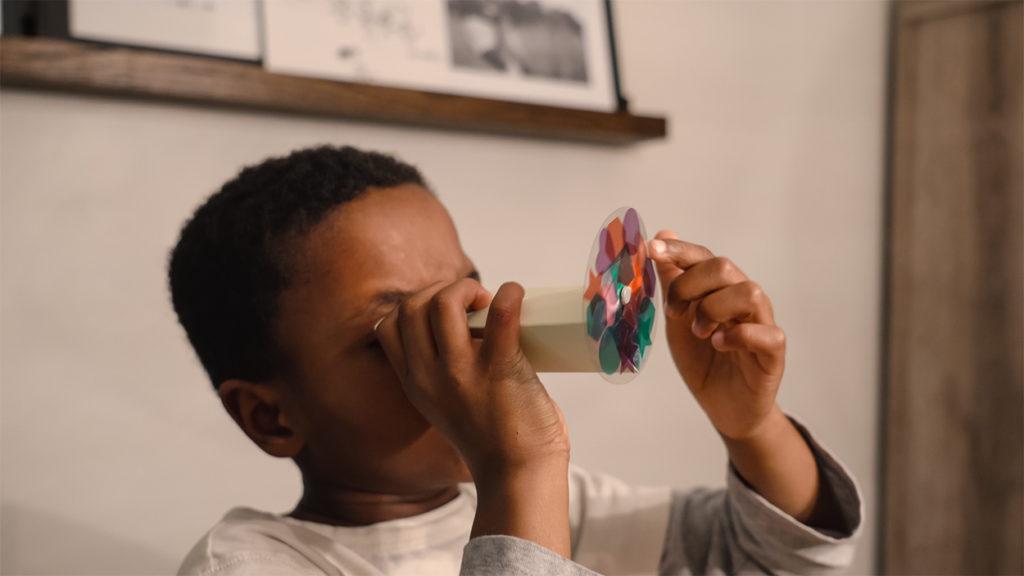 A kid looking through a Kiwi Crate Kaliedoscope