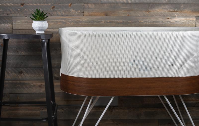 The Snoo smart bassinet against a wall