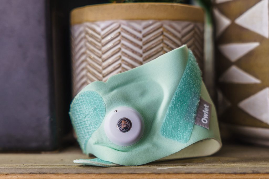 An Owlet 3rd generation Smart Sock on a table