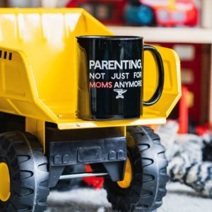 A Parenting, not just for moms anymore mug on a child's dump truck