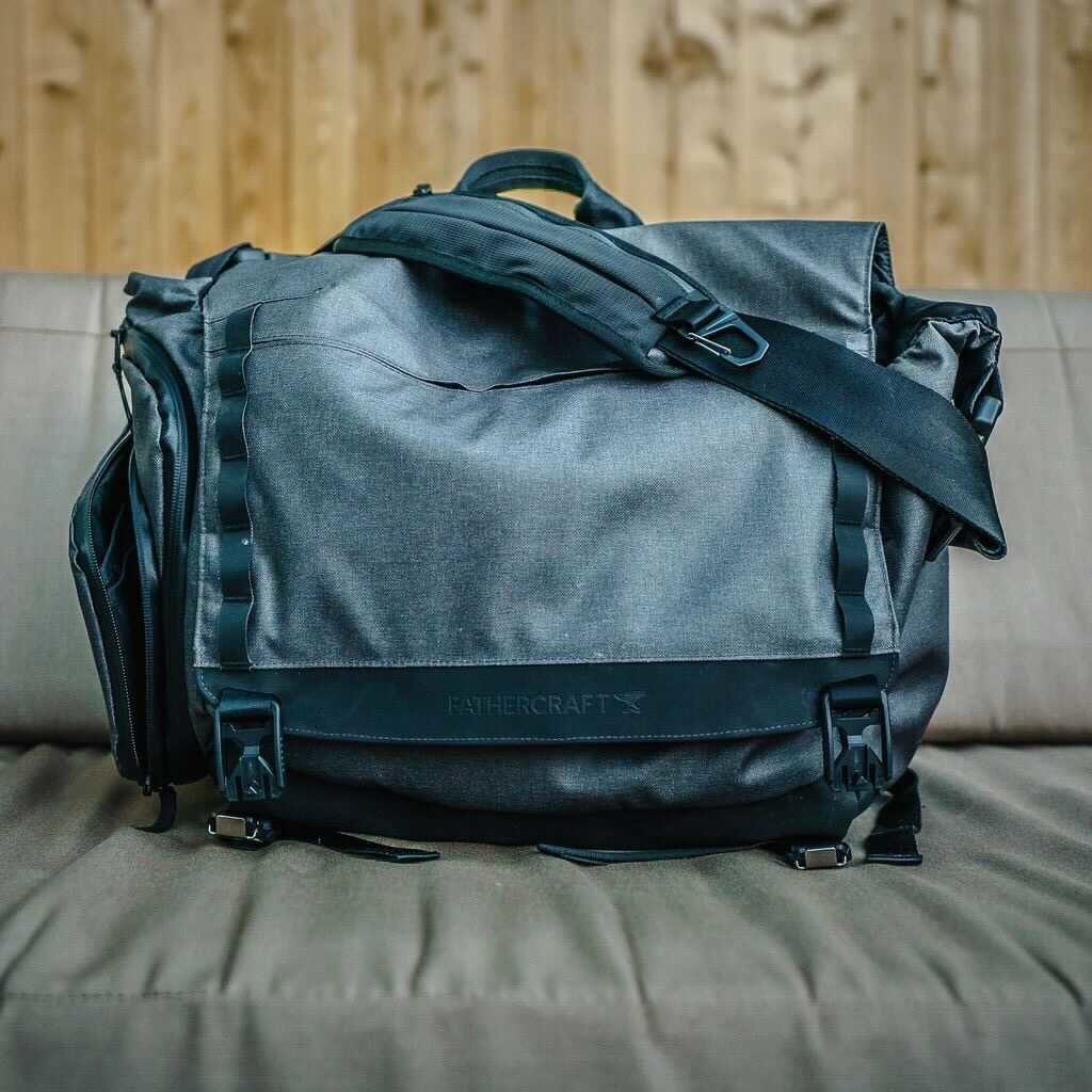 The Fathercraft diaper bag for dads on a couch in front of a wooden wall