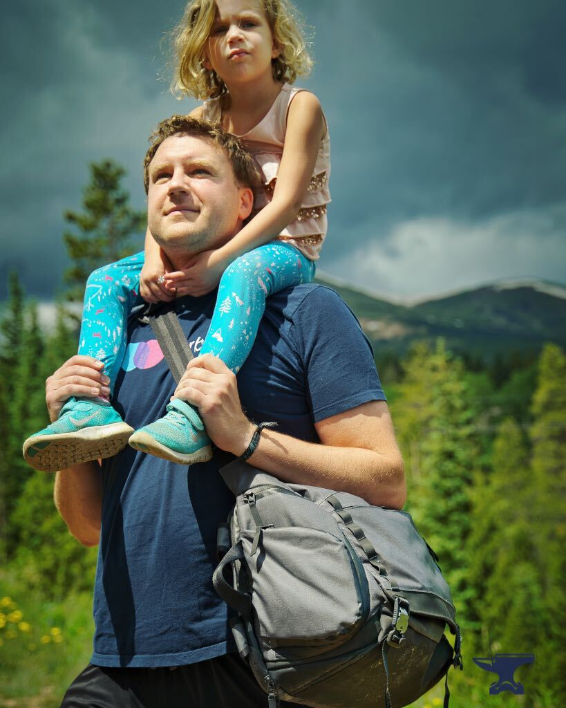 A dad with his kid riding on his shoulders and the Fathercraft diaper bag in messenger mode